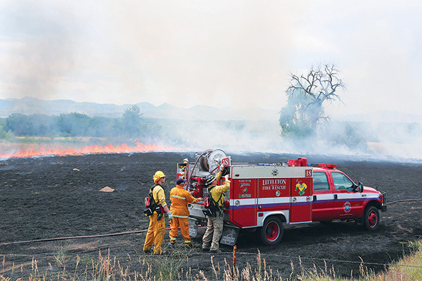 Firefighters with truck in burning field