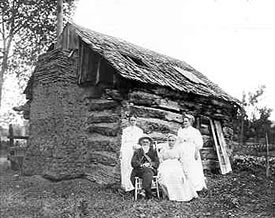 McBroom Cabin 1910. Isaac McBroom, brother of John; and Isaac's wife Emma. Also daughter of Isaac and Mrs. Etta Neuiheiser, who was in the same wagon train crossing the plains.