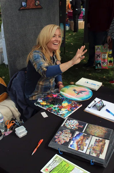 Craft vendor demonstrates her painting techniques at the Friends Craft Fair