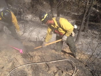 Wildland fire team uses hand tools to combat fire