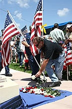 Member of the Patriot Guard leaves a rose at the memorial