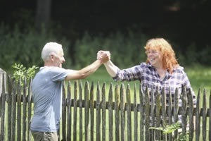 Two people shaking hands over a fence