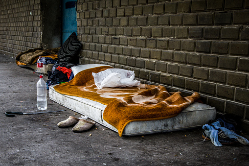 The camp of the homeless: a dirty matress, blanket, some food packacking and some shoes.
