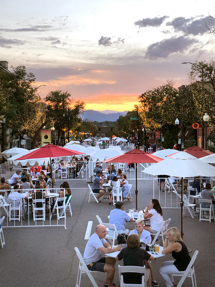 Weekends on Main guests eating at tables in the street looking west at sunset