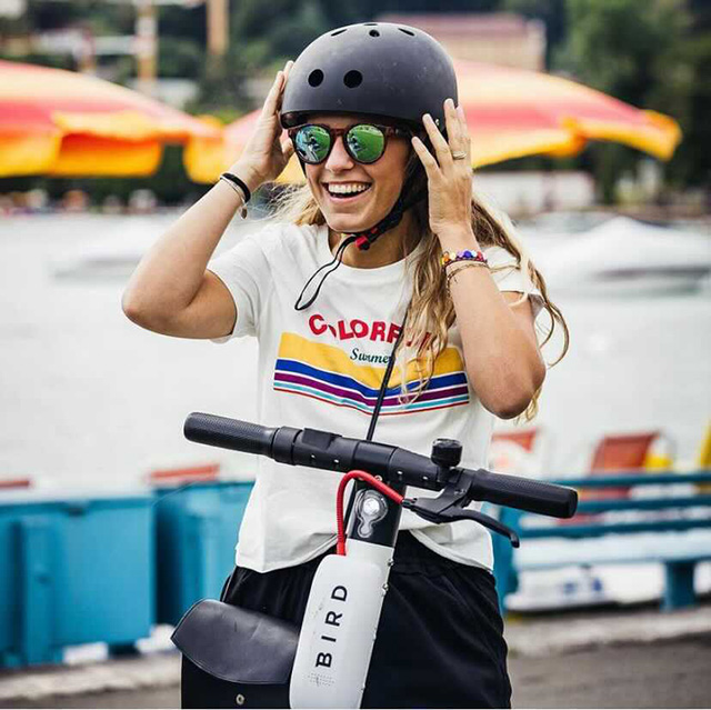 Girl adjusts her helmet before riding an electronic scooter
